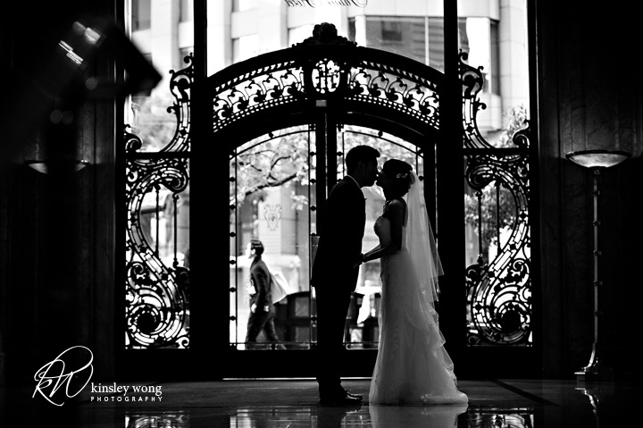 bride and groom black and white photo in front of main door at the palace hotel
