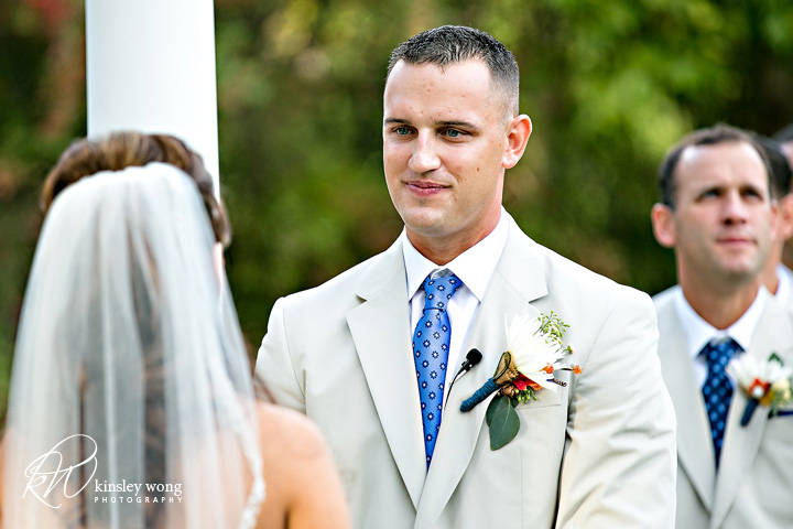 groom smiling at bride during the ceremony